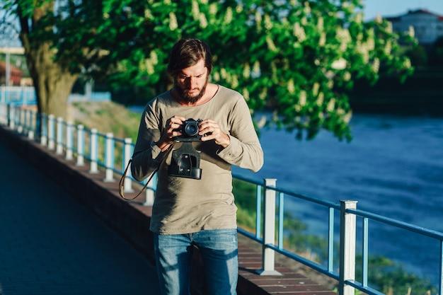 Homme heureux hipster occasionnel faisant photo à l'aide de la caméra rétro en plein air dans le parc
