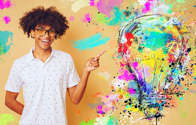 Un homme heureux avec des lunettes indique quelque chose avec la main