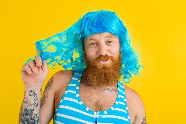 Un homme heureux avec un maillot de bain bouée de sauvetage et une perruque bleue agit comme une femme heureuse