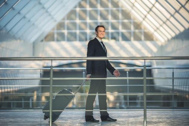 L'homme heureux marche avec une valise dans le centre d'affaires