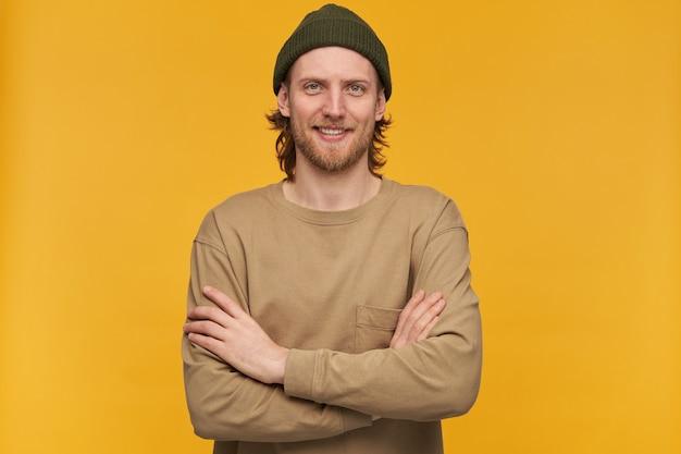 Homme heureux, mec positif aux cheveux blonds, barbe et moustache. porter un bonnet vert et un pull beige. tient les bras croisés sur une poitrine. isolé sur mur jaune