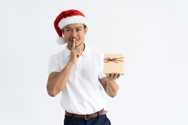 Homme heureux, montrant la boîte-cadeau et le geste de silence