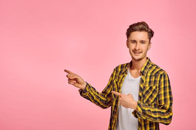 Homme heureux montre sur le mur, fond rose, émotion