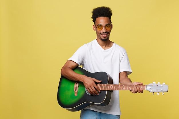 Homme heureux musicien afro-américain, posant avec une guitare, sur fond jaune doré.