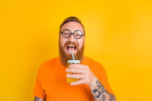 L'homme heureux de nerd avec des verres boit un jus de fruit