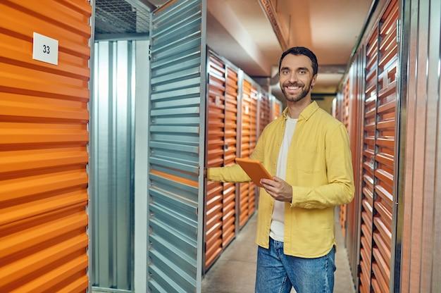 Homme heureux ouvrant la porte au conteneur d'entrepôt