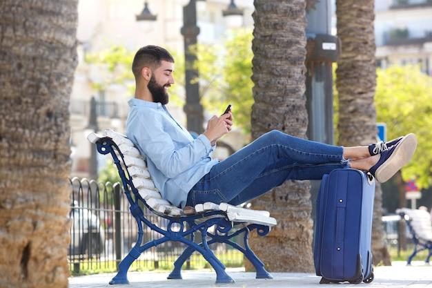 Homme heureux pleine longueur avec téléphone portable et valise assis sur un banc