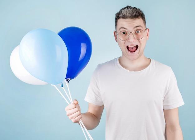 Un homme heureux porte des ballons colorés, porte des lunettes. un étudiant joyeux vient à la fête sortante