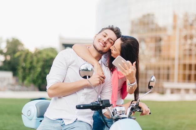 Homme heureux posant sur scooter pendant que son ami l'embrasse