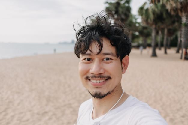 L'homme heureux prend le selfie avec le palmier sur le concept de voyage d'été de plage