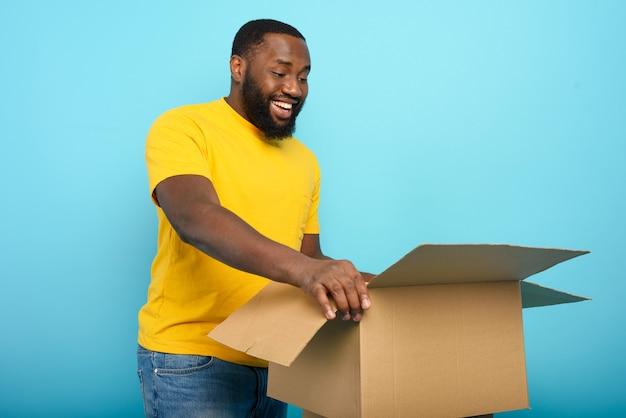Un homme heureux reçoit un colis de la commande de la boutique en ligne