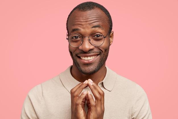 Un homme heureux regarde curieusement la caméra, a un large sourire, garde les mains jointes dans un geste intrigant, remarque quelque chose de souhaitable