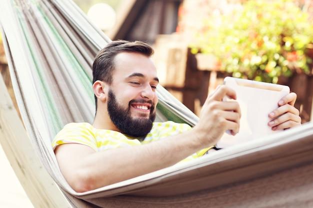Homme heureux reposant sur un hamac avec tablette