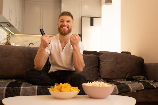 Un homme heureux s'assoit sur un canapé et regarde la télévision ou un film. jeune homme barbu européen tenant la télécommande. bols avec chips et pop-corn sur table. concept de repos à la maison. intérieur du studio