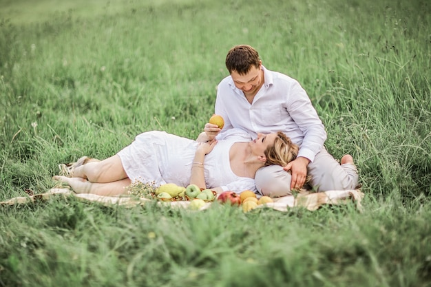 Homme heureux avec sa femme enceinte reposant sur la pelouse un jour d'été.