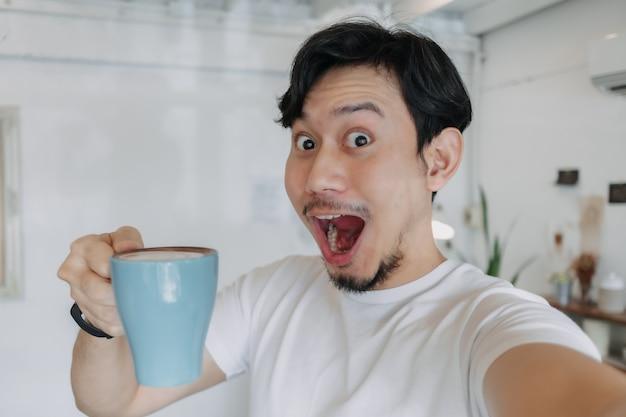 Un homme heureux savoure son café et se selfie avec sa tasse de café