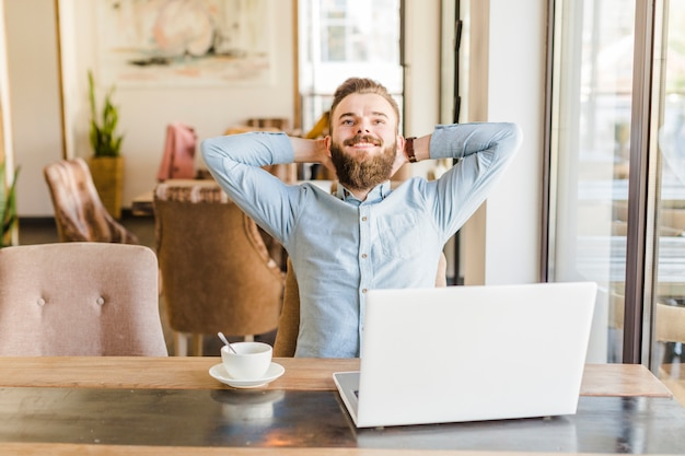 Homme heureux se détendre dans un café avec une tasse de café et un ordinateur portable sur le bureau