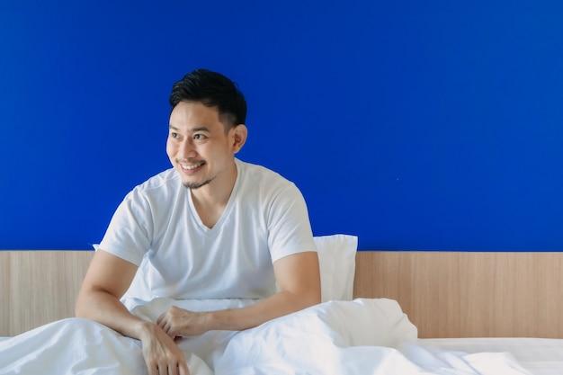 Un homme heureux se réveille sur son lit sur fond d'espace de copie bleu