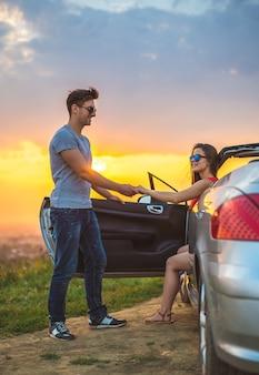 L'homme heureux se tient près d'une femme en cabriolet sur fond de soleil éclatant