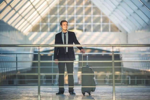 L'homme heureux se tient avec une valise dans le centre d'affaires