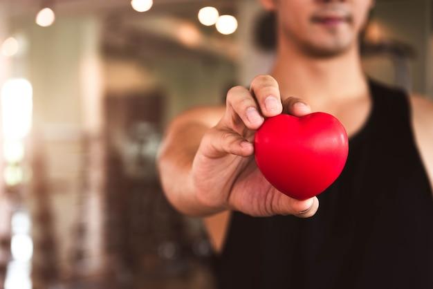 Homme heureux sport tenant coeur rouge au club de gym fitness. mode de vie d'entraînement cardio-cardiaque médical.