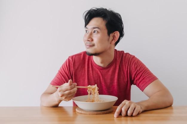 Un homme heureux en t-shirt rouge mange des nouilles instantanées avec un fond blanc