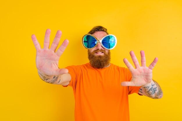 Homme heureux avec tatouage de barbe et grandes lunettes de soleil