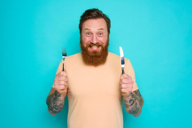 Un homme heureux avec des tatouages est prêt à manger avec des couverts à la main