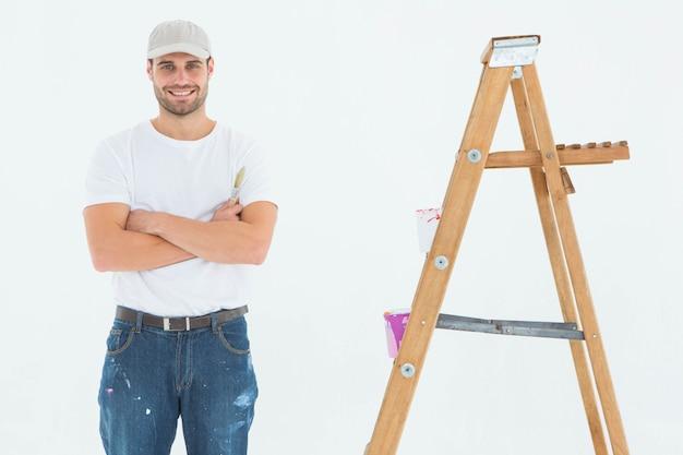 Homme heureux, tenant rouleau peinture, debout, par, échelle