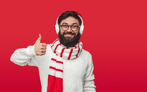 Homme heureux en tenue d'hiver et casque montrant le pouce vers le haut
