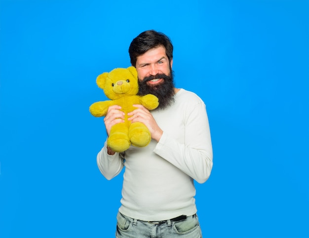 L'homme heureux tient la célébration de vacances d'ours en peluche jouet en peluche homme souriant embrasse l'anniversaire de l'ours en peluche ou