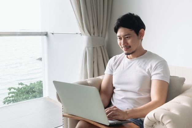 Un homme heureux travaille à l'hôtel avec un concept de séjour avec vue sur la mer