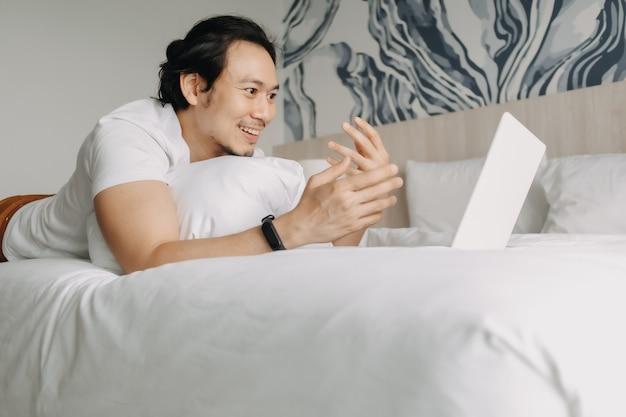 Un homme heureux travaille avec un ordinateur portable sur le lit dans le concept de travail de l'hôtel
