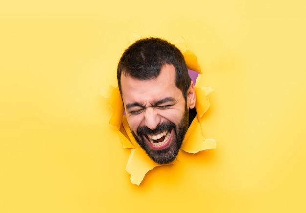 Homme heureux à travers un trou de papier