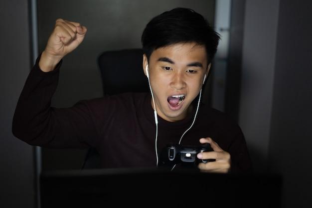Homme heureux en utilisant le joystick pour jouer à des jeux