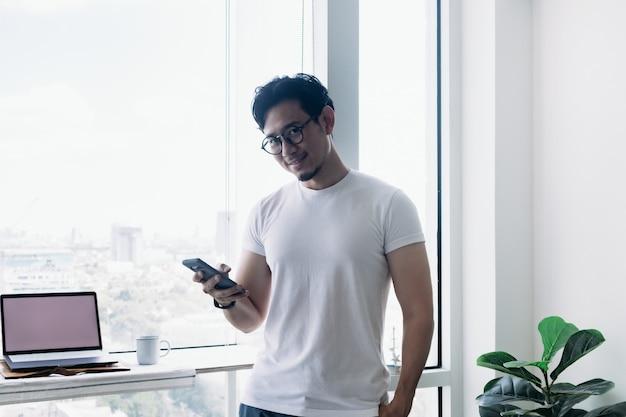 Un homme heureux utilisant un smartphone avec un concept de vue sur le balcon travaille à domicile
