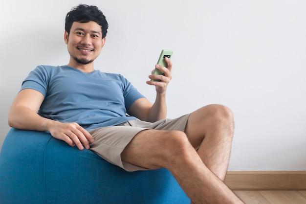 Un homme heureux utilise un smartphone tout en s'asseyant et en se détendant sur le sac de haricots