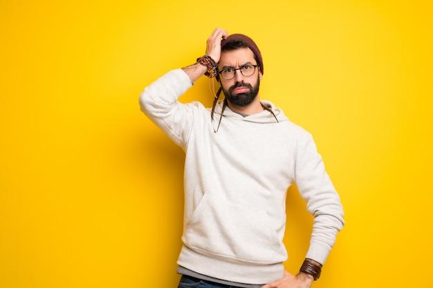 Homme hippie avec des dreadlocks avec une expression de frustration et de non compréhension