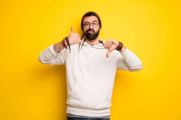 Homme hippie avec des dreadlocks faisant bon signe. indécis entre oui ou non