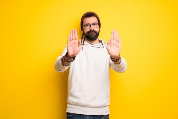 Homme hippie avec des dreadlocks faisant un geste d'arrêt pour déçu par un avis