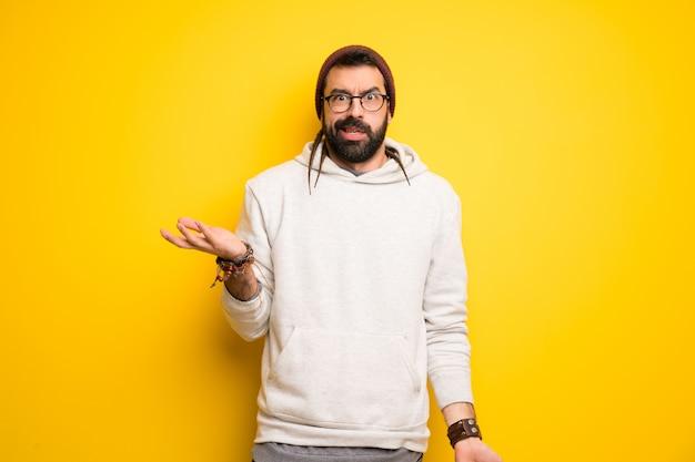 Homme hippie avec des dreadlocks malheureux et frustré par quelque chose parce que ne comprend pas quelque chose