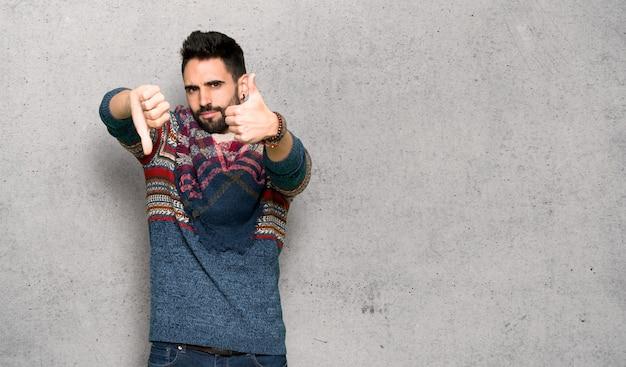 Homme hippie faisant bon signe. indécis entre oui ou non sur un mur texturé