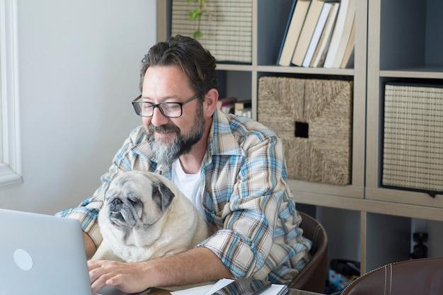 Homme hipster avec barbe travaille à la maison sur un ordinateur portable et une connexion internet avec son ami vieux chien ensemble sur le bureau