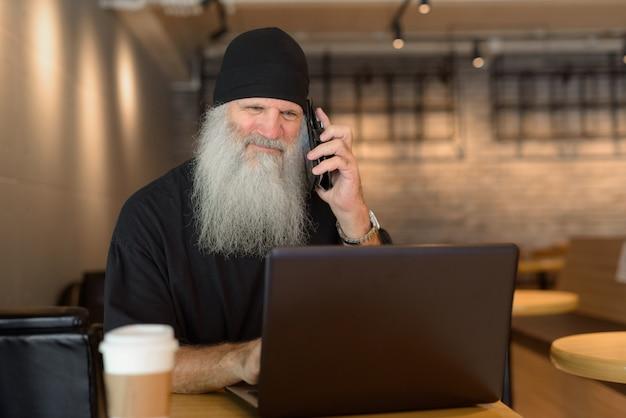 Homme hipster barbu mature à l'aide de téléphone et ordinateur portable à l'intérieur du café