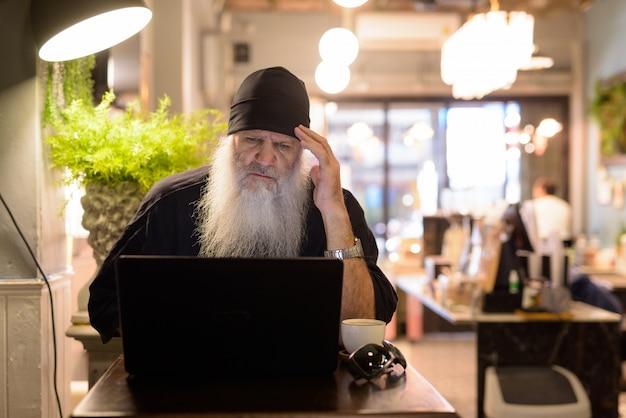 Homme hipster barbu mature stressé ayant des maux de tête tout en utilisant un ordinateur portable au café
