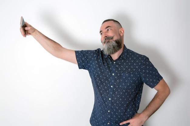 Homme hipster barbu prend un selfie isoalted sur fond blanc