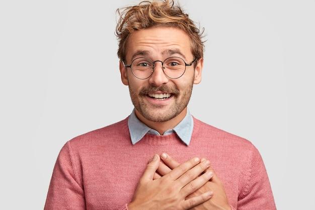 Un homme hipster de bonne humeur garde les mains sur la poitrine, a une expression faciale positive, une coiffure bouclée à la mode, étant reconnaissant envers les invités