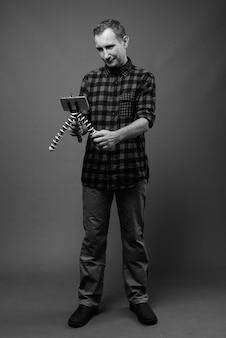 Homme hipster contre mur gris en noir et blanc