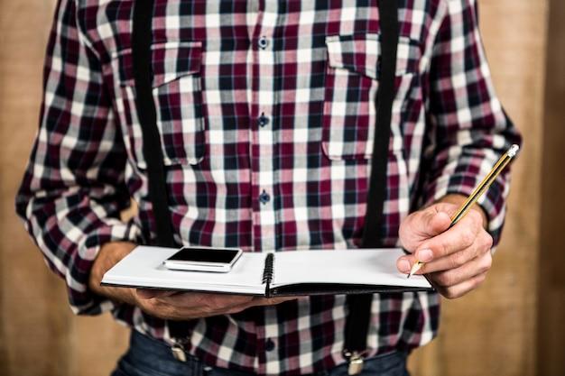 Homme hipster écrit sur un cahier