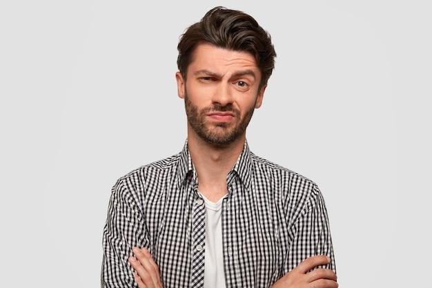 Homme hipster élégant garde les bras croisés, regarde avec une expression hésitante, lève les sourcils avec étonnement